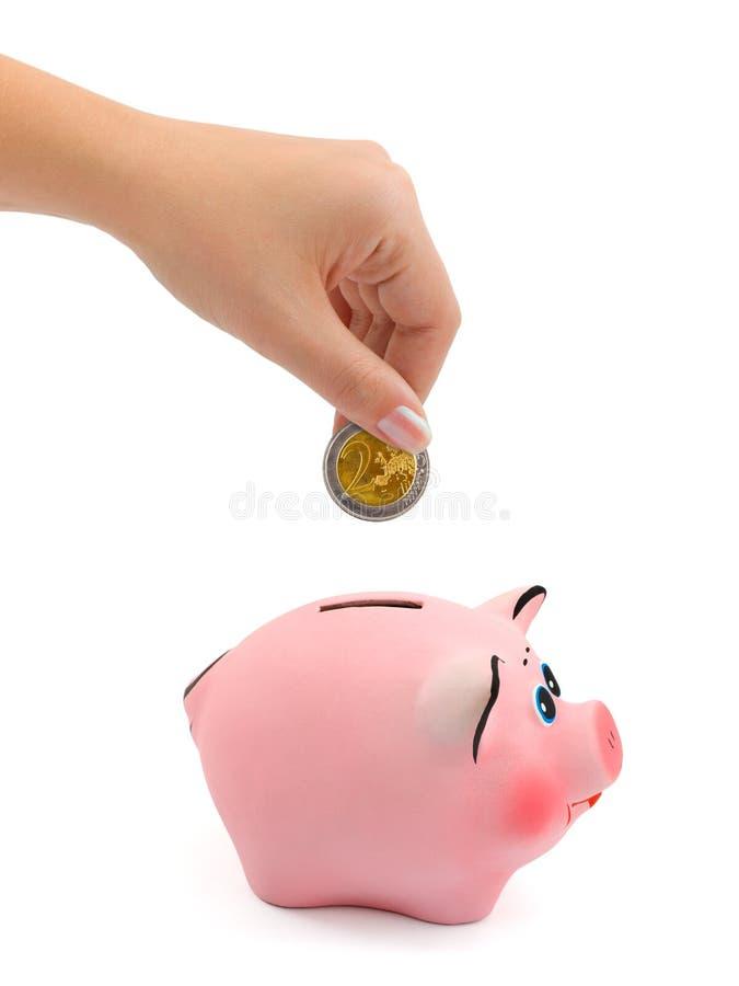 Spaarvarken en hand met muntstuk stock fotografie