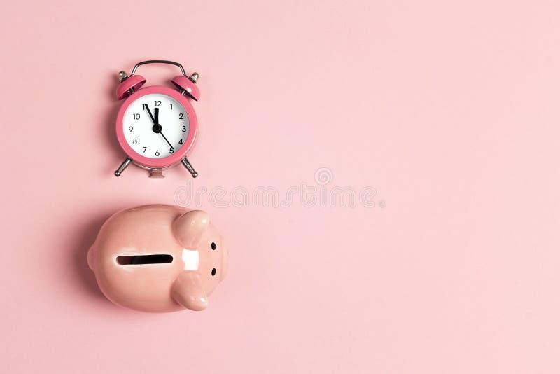 Spaarvarken en klassieke wekker op roze achtergrond Tijd aan besparing, geld, bankwezenconcept stock foto