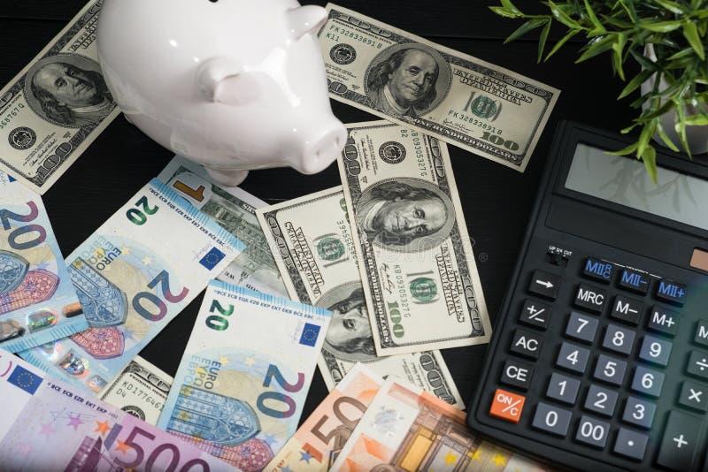 Spaarvarken met contant geld en calculator op bedrijfsdocumenten royalty-vrije stock foto