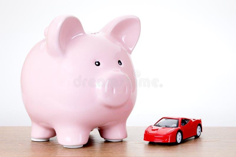 Spaarvarken met een kleurrijke rode modelstuk speelgoed auto royalty-vrije stock afbeeldingen