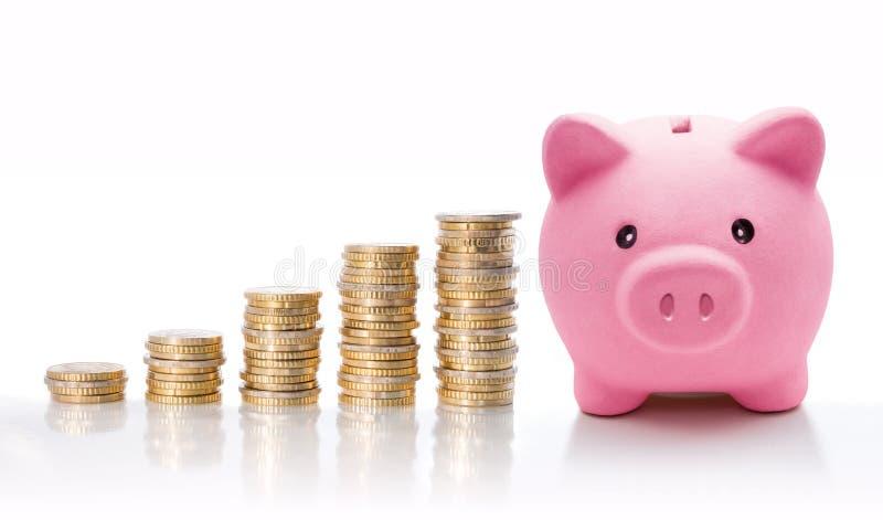 Spaarvarken met euro muntstukstapels - concept verhoging royalty-vrije stock afbeeldingen