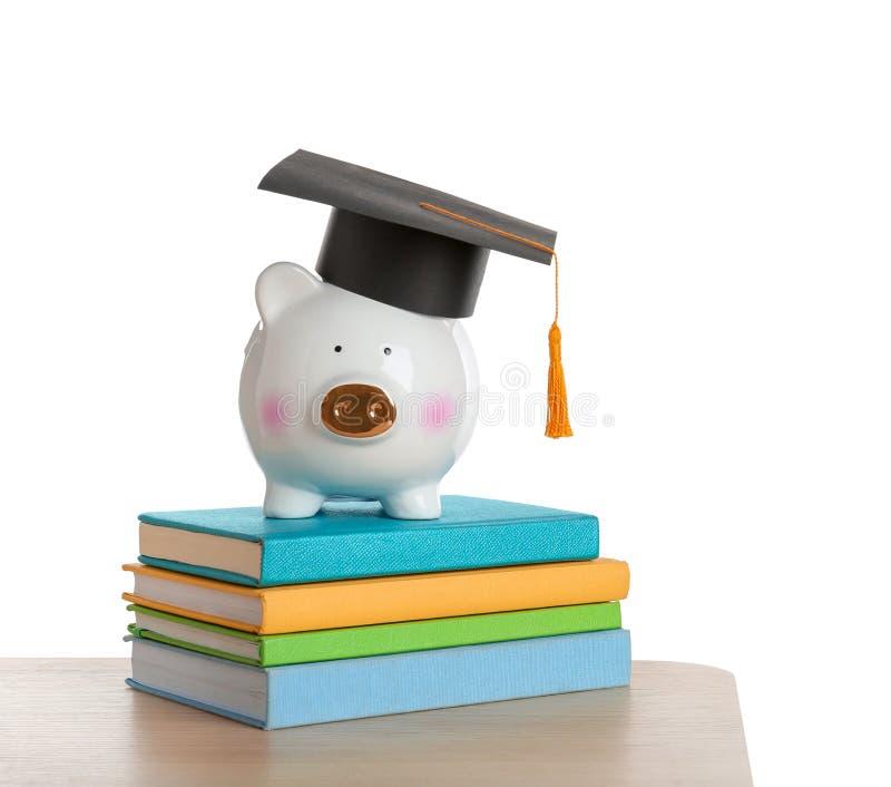 Spaarvarken met graduatiehoed en boeken op lijst royalty-vrije stock foto's