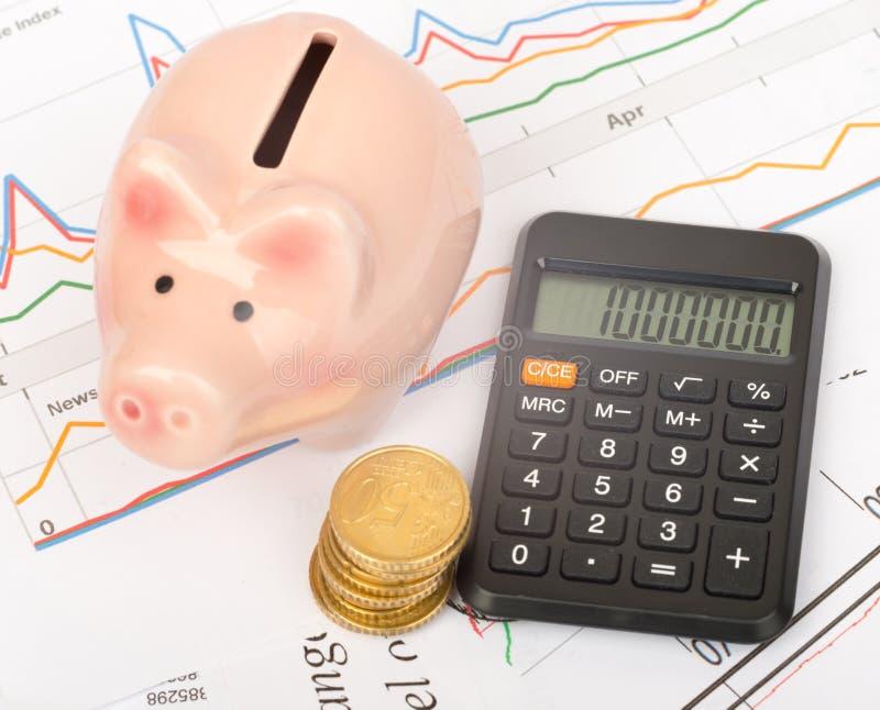 Spaarvarken met muntstukken en calculator stock afbeelding