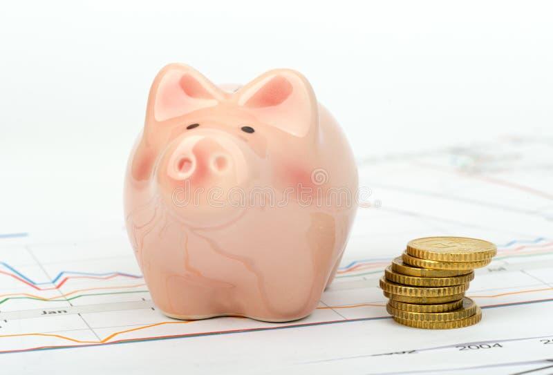 Spaarvarken met muntstukken op bedrijfsdocumenten royalty-vrije stock fotografie