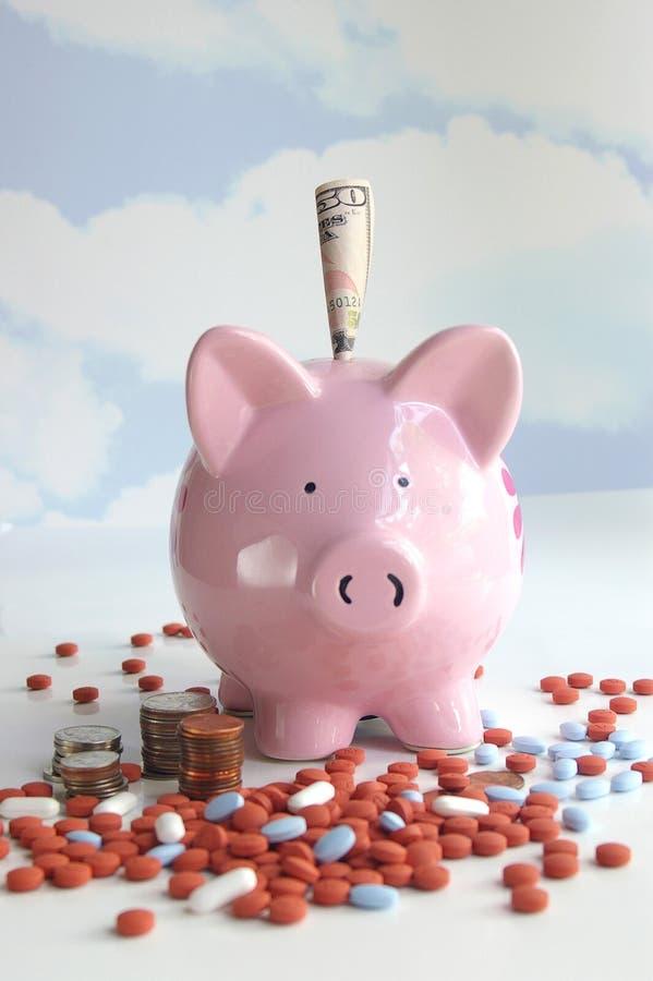 Spaarvarken met pillen en geld stock fotografie
