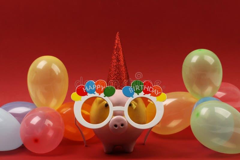 Spaarvarken met zonnebril Gelukkige verjaardag, partijhoed en multicolored partijballons op rode achtergrond royalty-vrije stock afbeeldingen