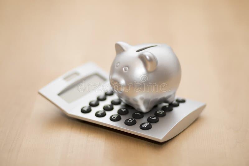 Spaarvarken op calculator stock afbeelding