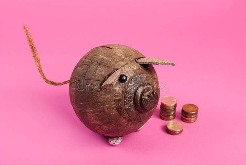 Spaarvarken van kokosnoot en metaal geïsoleerd muntstuk wordt gemaakt op roze dat stock foto's