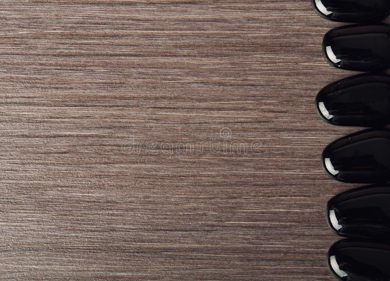 Spabakgrund. svarta stenar på trä royaltyfria foton
