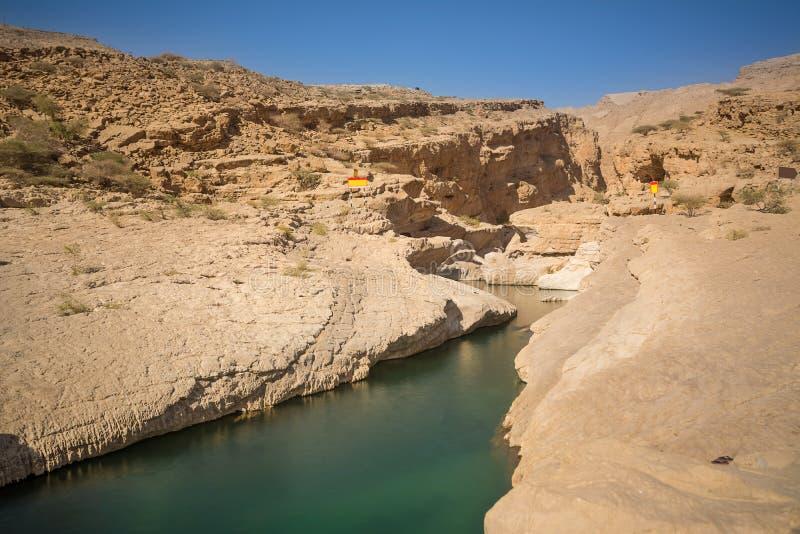 Spaccando in roccia con acqua a Wadi Bani Khalid Oman immagine stock libera da diritti