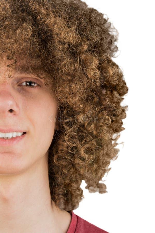 Spacchi in mezzo ritratto potato di giovane uomo europeo riccio con capelli ricci lunghi e un primo piano vago di sorriso capelli immagine stock