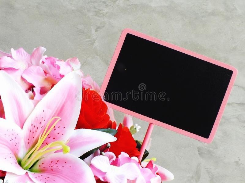 Space background with bouquet of flowers and empty wooden tag stock images