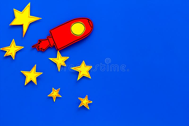 Space flight or space travel concept. Drawn stars and rocket or space shuttle on blue background top view copy space royalty free stock images