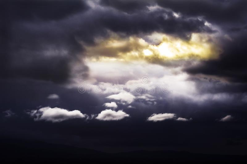 A space of light in a sky full of dark clouds royalty free stock photo