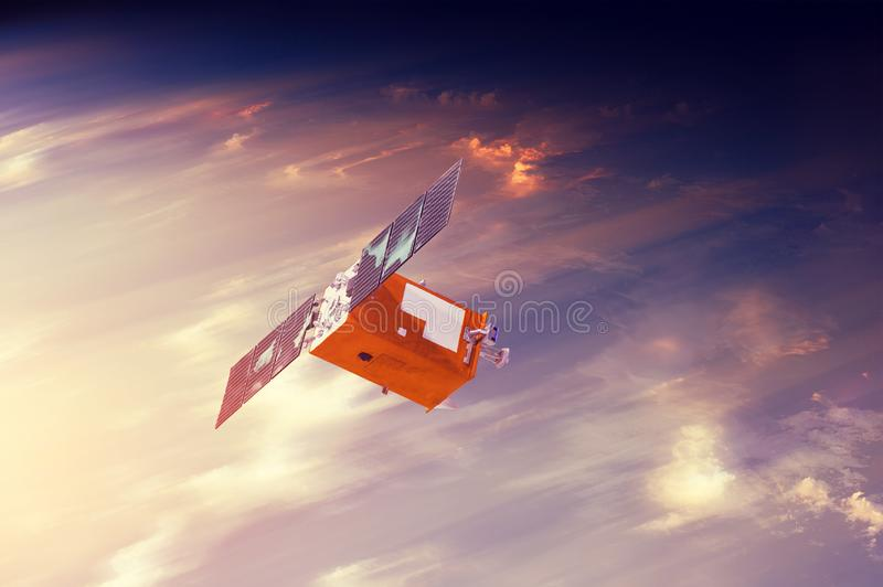 Space satellite flying in orbit over sunset clouds orbiting Earth. Bright light from the sun and glare. Elements of this image stock images