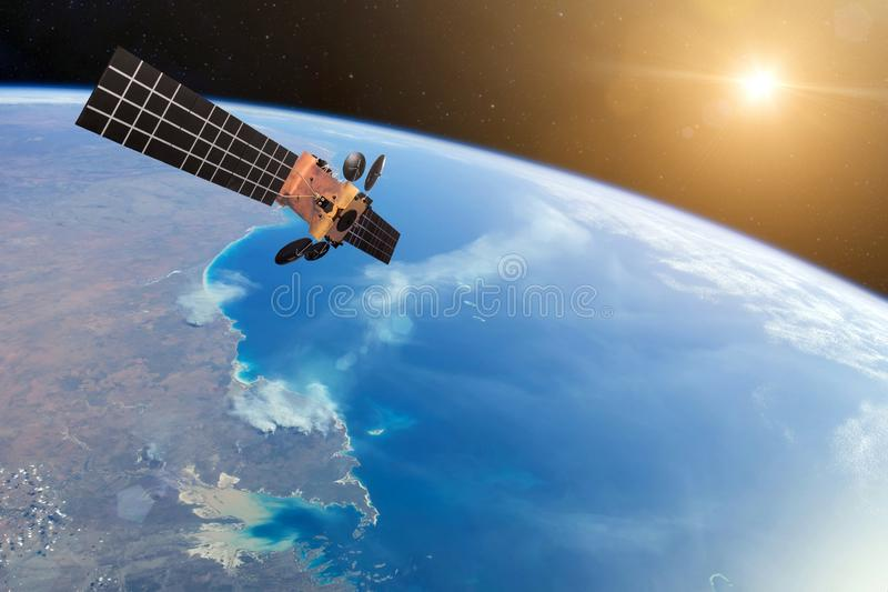 Space satellite orbiting the earth and bright lights Sun. Elements of this image furnished by NASA.  royalty free stock images