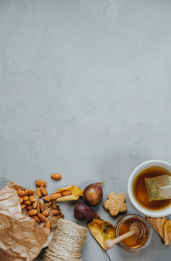 Space for text, Flat lay, Herbal tea, almonds, grapes, honey, figs, dry leaves, lavender on a gray background. Autumn concept, to stock image