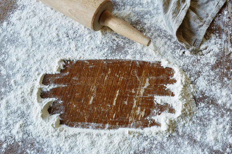 Space wiped in flour in vivid kitchen scene. Creative space for recipe baking roll and flour on wooden table royalty free stock photography
