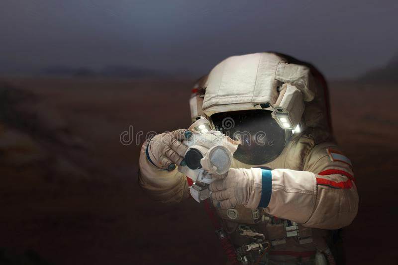 Spaceman with a camera in a space suit on the planet Mars. Astronaut takes pictures a new planet royalty free stock images