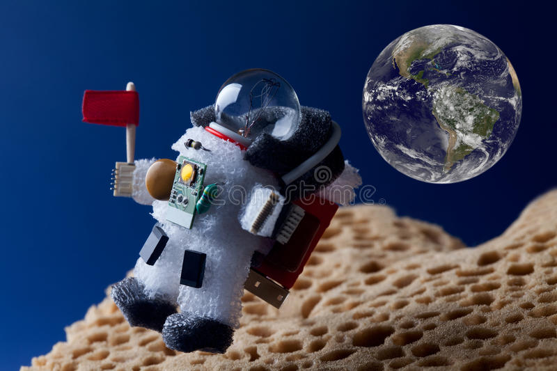 Spaceman floating stratosphere, planet earth and blue sky as backdrop. Light bulb toy character dressed in spacesuit royalty free stock photography