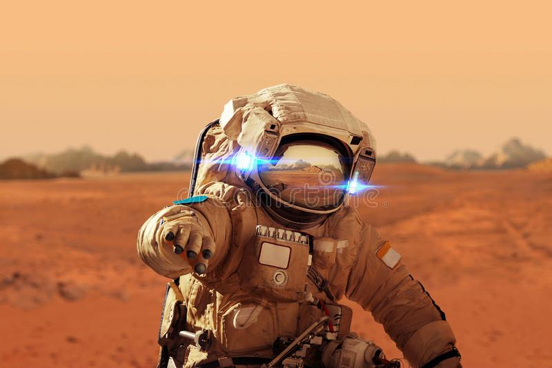 Spaceman walks on the red planet Mars. Space Mission. royalty free stock photos