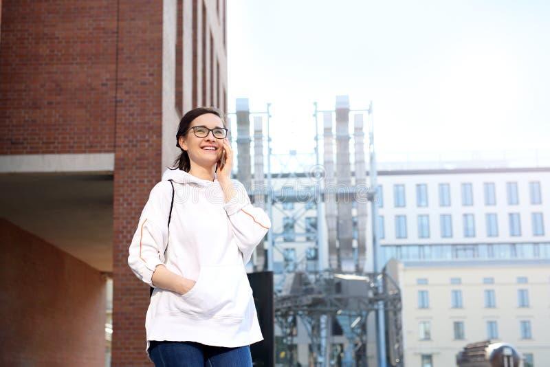 Spacer w centrum miasta, m?odej kobiety odprowadzenie woko?o miasta opowiada na telefonie kom?rkowym obraz stock