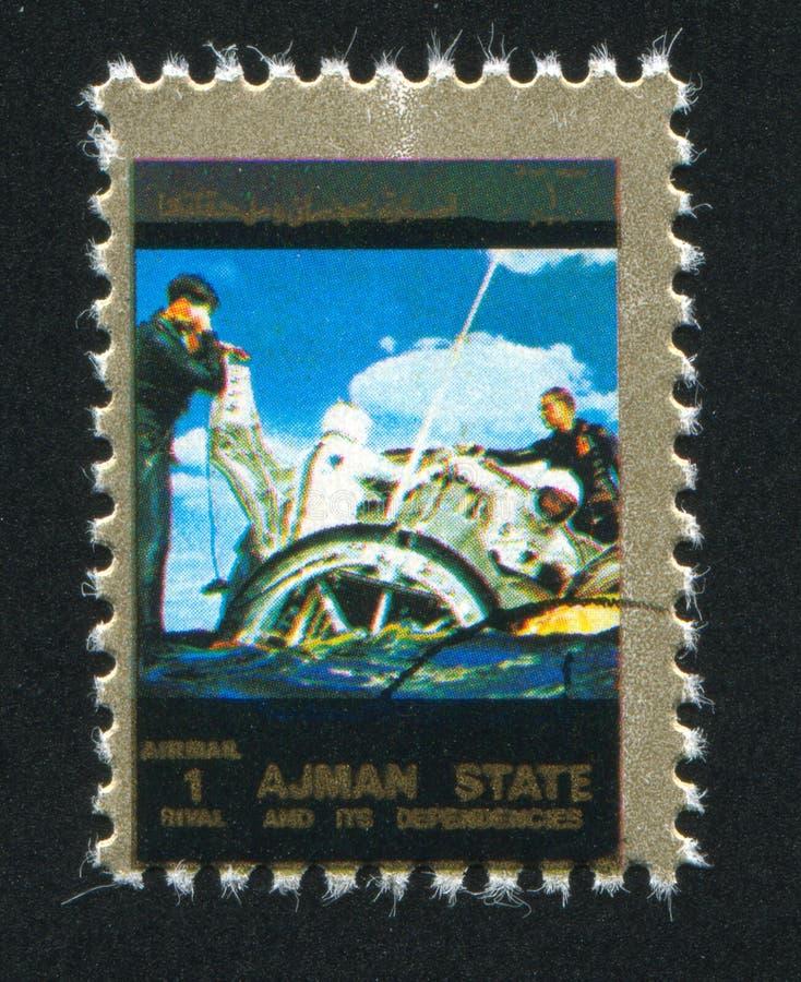 Spaceship landing. AJMAN - CIRCA 1976: stamp printed by Ajman, shows Spaceship landing, circa 1976 royalty free stock photography