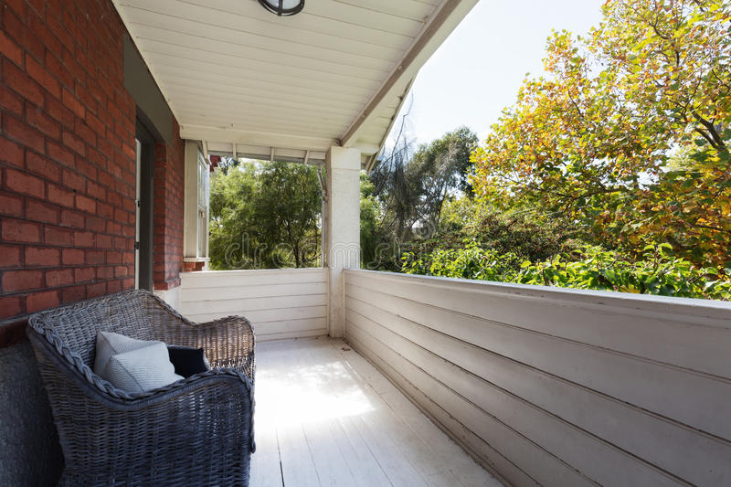 Spacious apartment balcony with view to the tree tops. From cane wicker seat stock photos