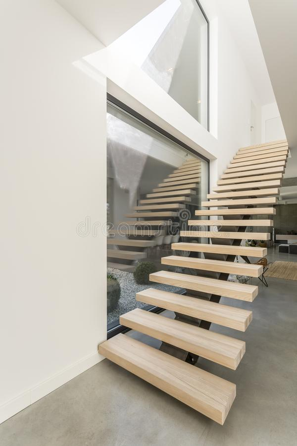 Spacious apartment with wooden stairs royalty free stock photo