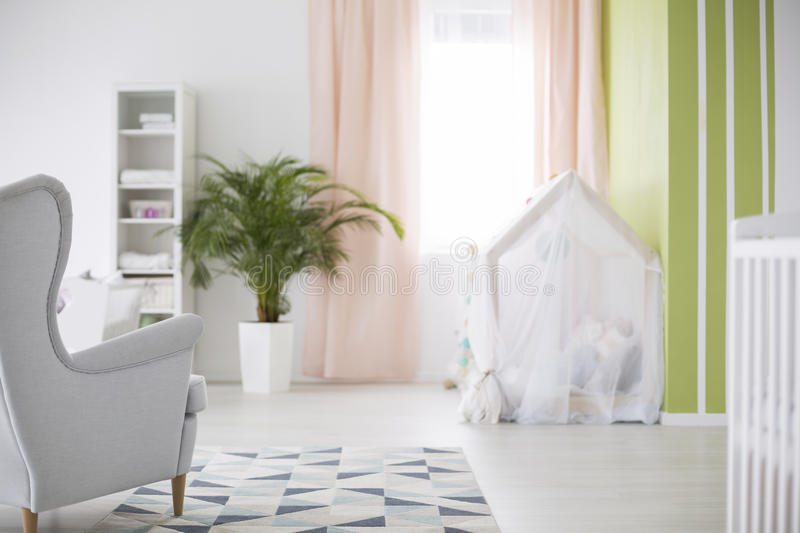 Spacious baby room. Spacious white baby room with armchair, plant and crib royalty free stock images