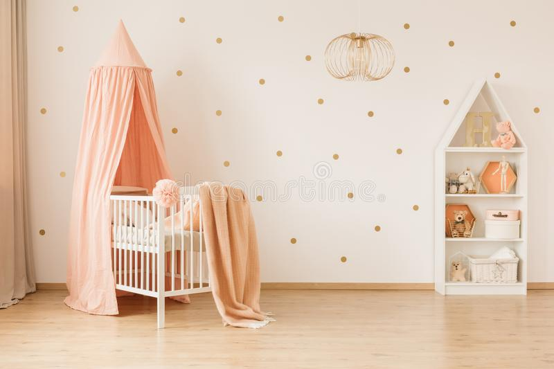 Spacious baby`s bedroom interior. Gold lamp in spacious baby`s bedroom interior with canopied pink crib against wallpaper royalty free stock photos