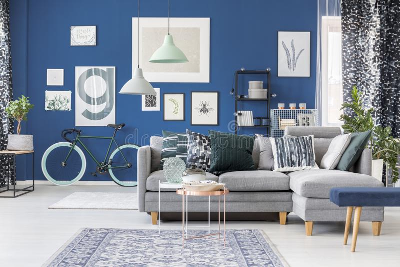 Spacious blue living room. Copper table on carpet in front of grey corner settee with pillows in spacious blue living room stock photo