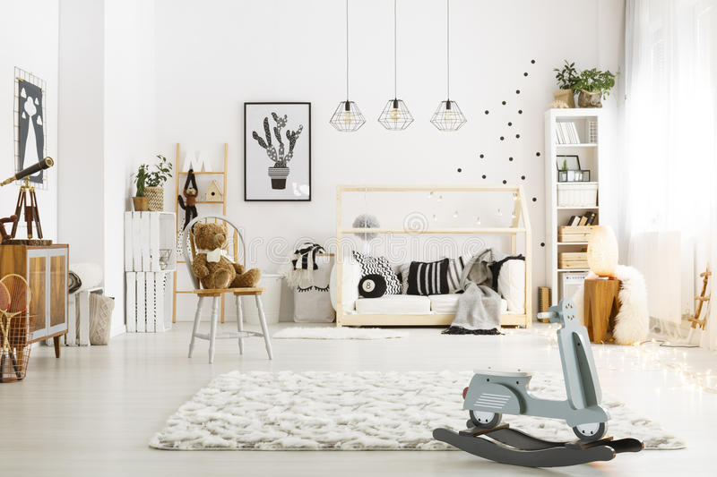 Spacious child room with bed. Chair, lamps and rocking scooter stock photo
