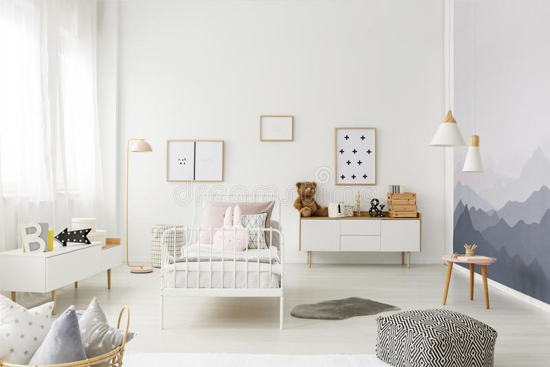 Spacious child`s bedroom interior. Patterned pouf in spacious child`s bedroom interior with rabbit pillow on white, metal bed royalty free stock photography