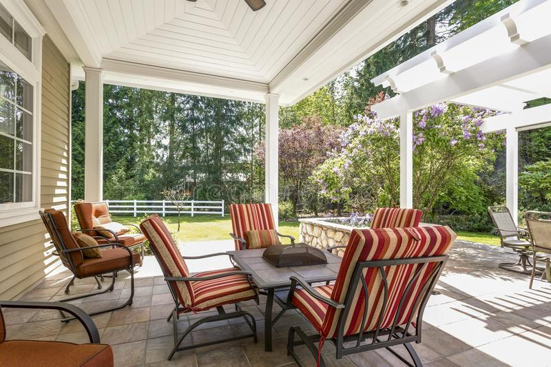 Spacious covered deck patio with table and red chairs. Spacious covered deck area with table and red outdoor chairs under white plank ceiling stock photography