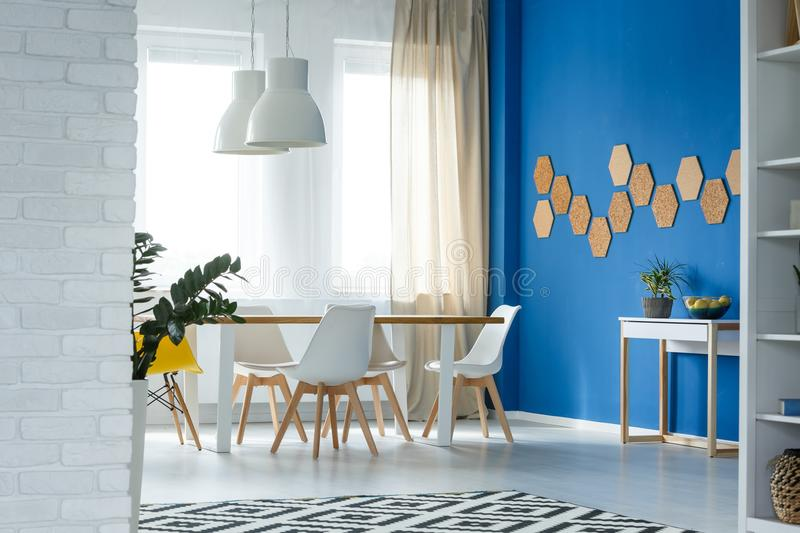 Spacious dining room with cork. Spacious dining room with white furniture and cork honeycombs decor on blue wall stock image