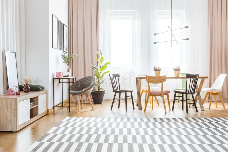 Spacious dining room with drapes. Spacious dining room interior with pink drapes and colorful chairs at the table standing against bright windows royalty free stock image