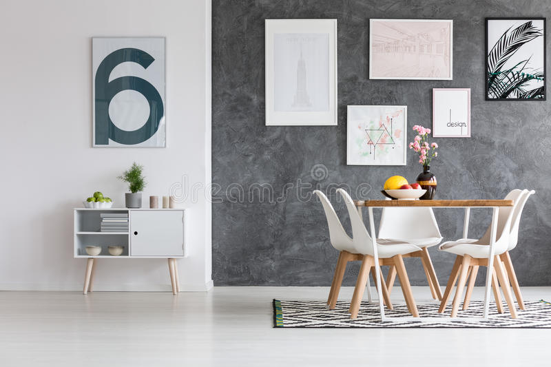 Spacious dining room with posters. On concrete dark wall and patterned carpet on glossy white floor stock image