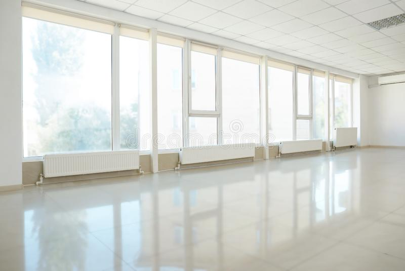 Spacious empty room with large windows stock photo