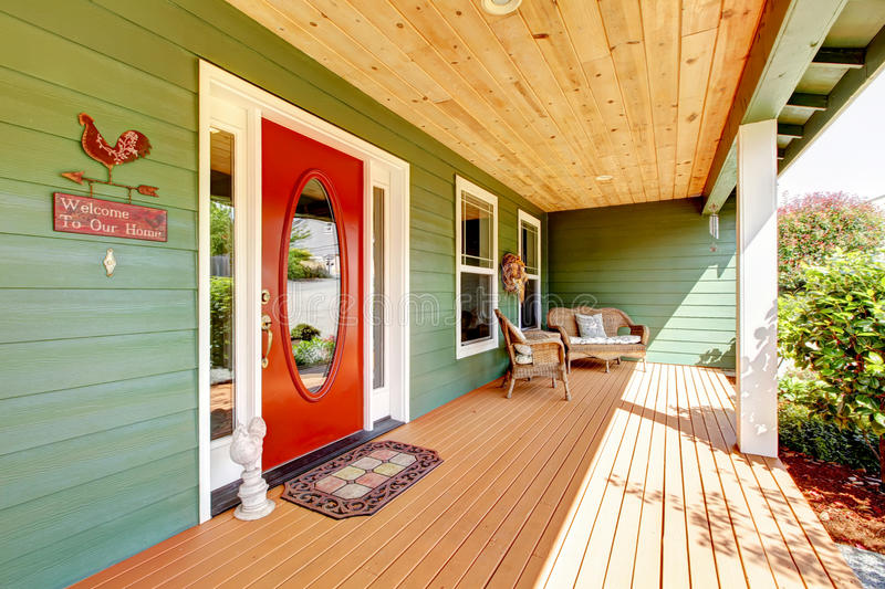 Spacious entrance porch with red door and wooden chair royalty free stock images
