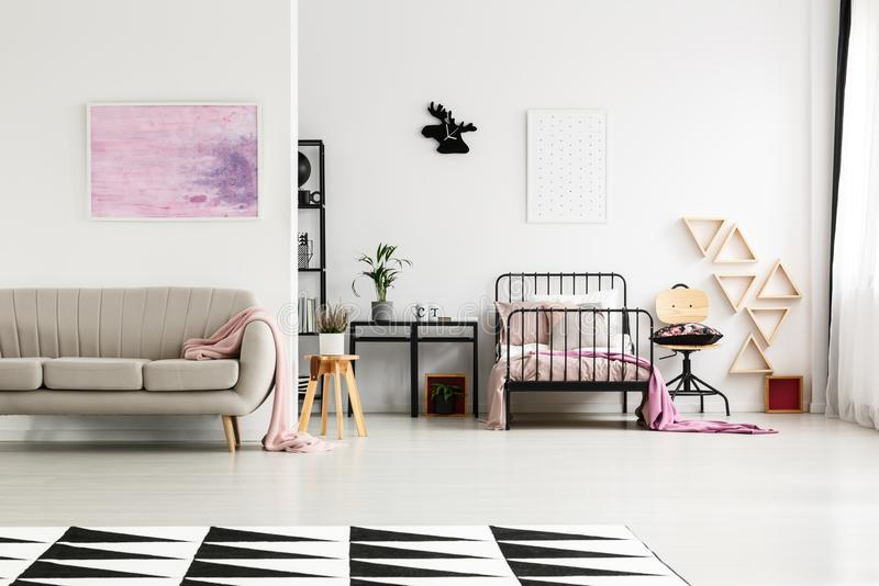 Spacious girl`s bedroom with chair. Pink painting above sofa in spacious girl`s bedroom with wooden chair next to bed and plant on stool royalty free stock image