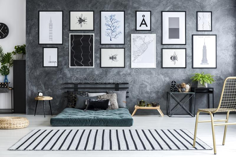 Spacious grey bedroom interior. Gold chair in spacious grey bedroom interior with green futon against concrete wall with posters royalty free stock images
