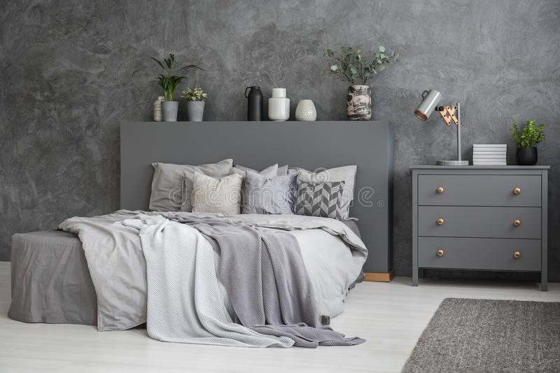Spacious grey and white bedroom interior with large bed with bed stock photo