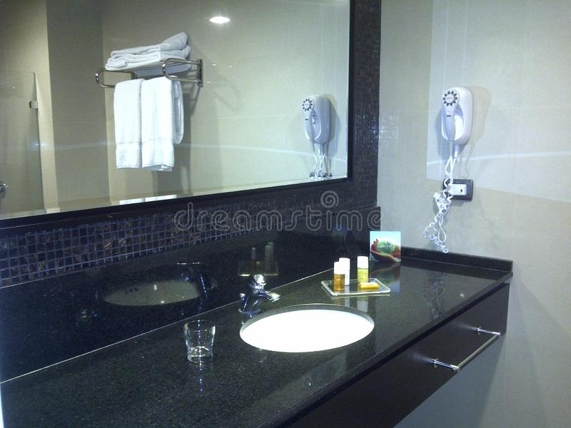 Spacious hotel bathroom in black and white tones with clean towels and hairdryer for the use of guests. royalty free stock photography
