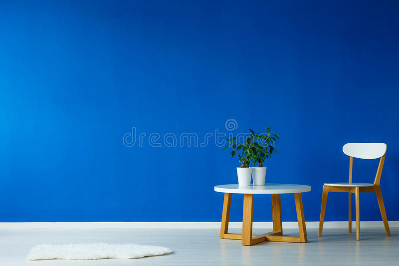 Spacious interior of living room. Spacious interior of a stylish scandinavian style living room with a chair, small table and plants stock images