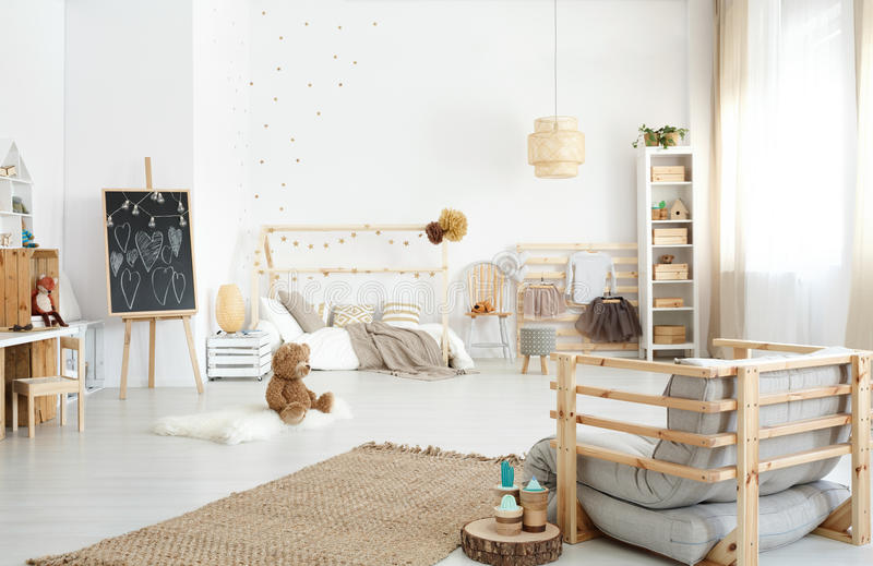 Spacious kid`s bedroom. Spacious modern kid`s bedroom with armchair, toys and diy accessories stock images
