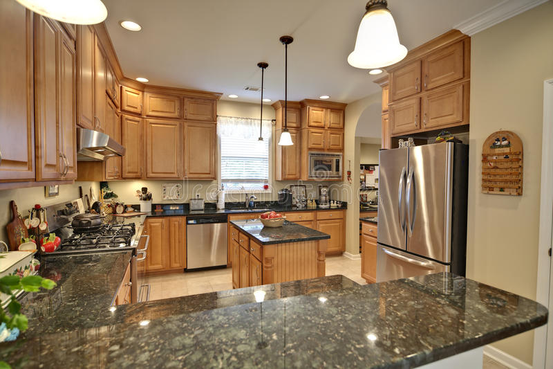 Spacious kitchen. Spacious modern kitchen with maple cabinets and granite royalty free stock photo