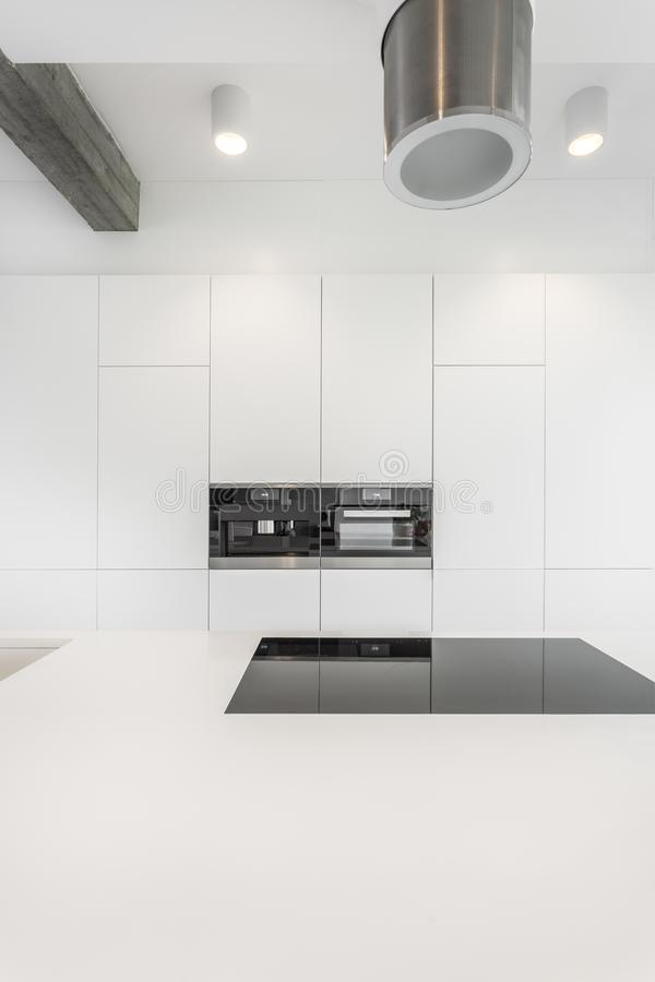 Spacious kitchen with designed hood stock image