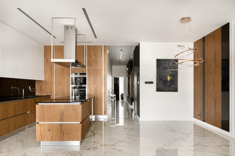 Spacious kitchen with island and wooden elements. Spacious kitchen in black and white with big kitchen island, wooden elements and marble floor stock photos