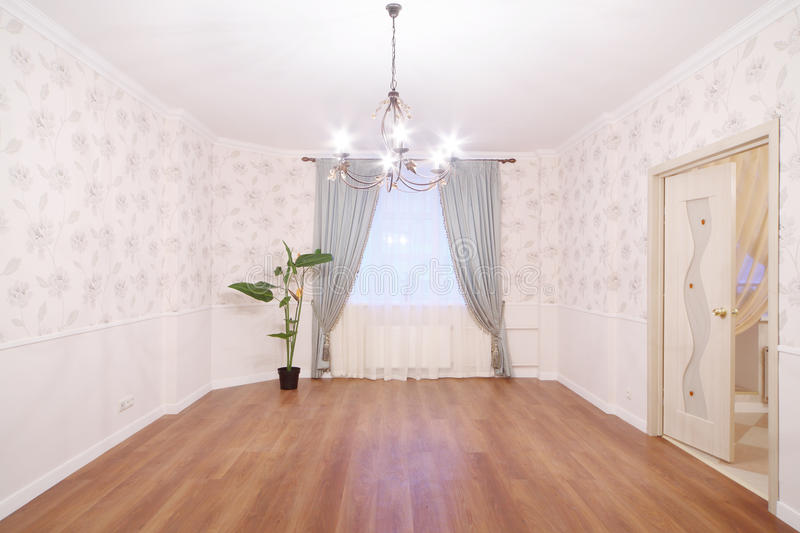 Spacious light room with chandelier and window royalty free stock image